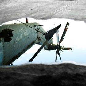A reflection of a Royal Navy Seaking tail in a puddle on the hangar floor.