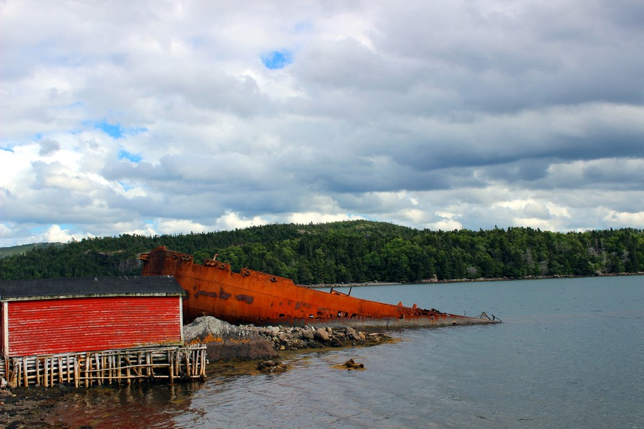 The beautiful clouds hang over the rusted boat down a side road in Newfoundland.