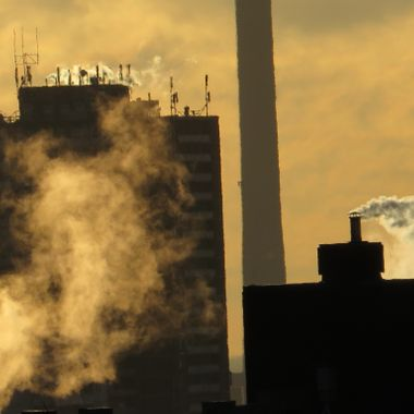 Observe the smoke-clad antennae on the building's roof. The image appears to display a sepia effect.