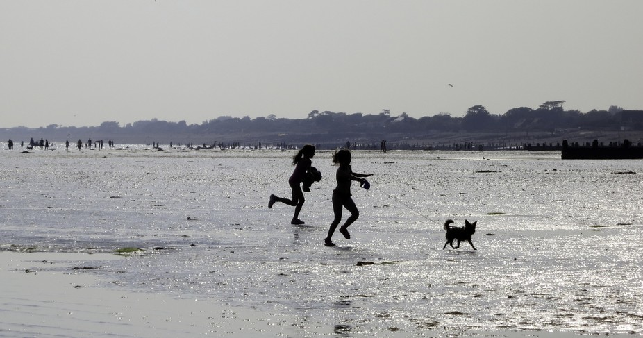 Two children run to keep up with their dog at Bognor Regis on the south coast of England