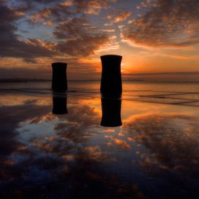 Clouds at the sunset have created an incredible structure that reflects in a puddle.