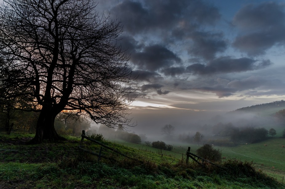 Shot at sunset with a field and village covered in fog in Langwieden Germany.