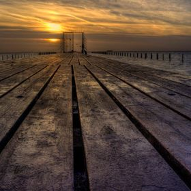 A long or one could say never ending wooden jetty extends into the sea. Sunset has created a beautiful golden light.