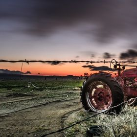 An old tractor sat by a fence holding a sign, the sunrise was in the distance and the clouds swiftly cruised over head from the gusting winds. Bi...
