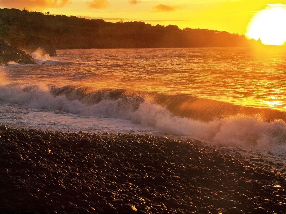 Sunrise on a black pebble beach on Maui