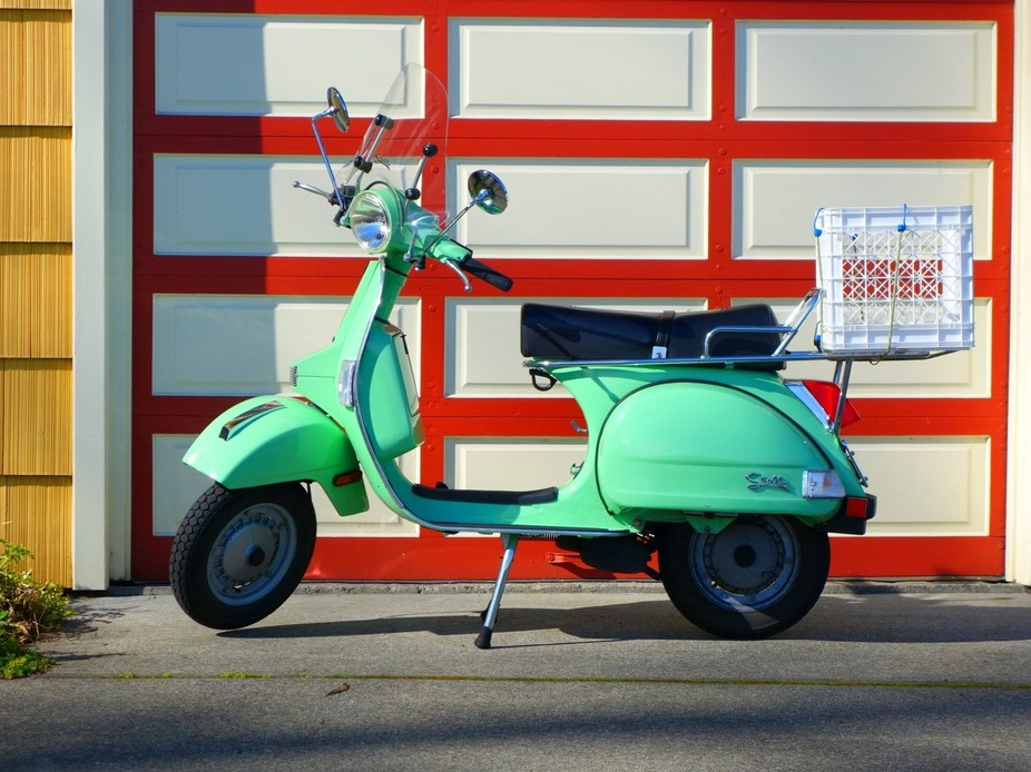 green moped in front of a cottage style home