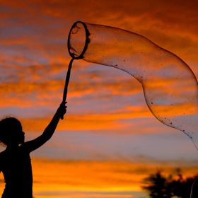 A young lady plays with bubbles in front of the July 4th Sunset