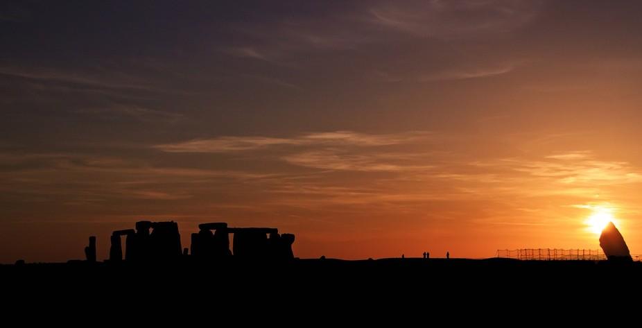 sunsetting behinde stonehendge with the hendge in silhouette