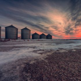 Dawn on the Saskatchewan prairie with silos juxtaposed by the morning sky.