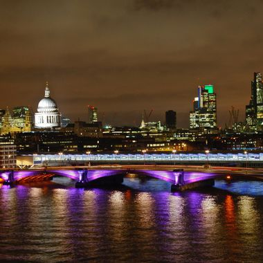 River Thames flowing through London at night, reflections from the bridge lights and cityscape in the background.