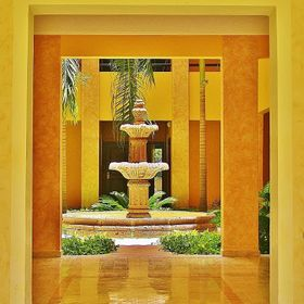 Surrounded by vibrant colors a fountain is framed perfectly by the entrance to entice a passerby.