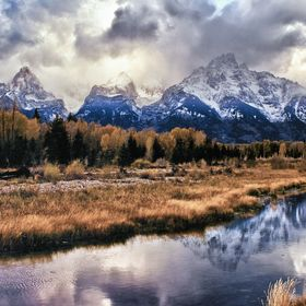 The setting sun illuminates the jagged peaks of the Tetons as an autumn storm rolls in.