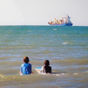Boys watch as Container Ship disappears over the horizon