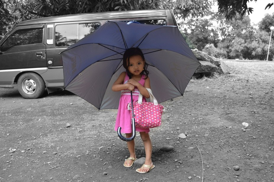 a little girl pretending to go to market with all her bag and umbrella.