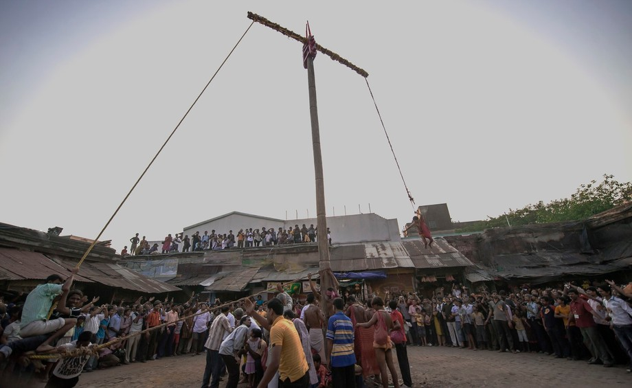 Devotees swing high in the air on tall poles for worshipping God Lord Siva on the Bengalee year e...
