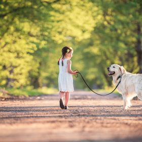 Young girl walking her dog in the park