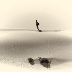 Vintage style photograph of a lone hiker crosses the top a white sand dune near Eucla Australia