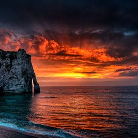 The sun rays behind some red clouds, in a dramatic color explosion, over the white cliffs of Etretat, in Upper Normandy. Coming back from the sho...