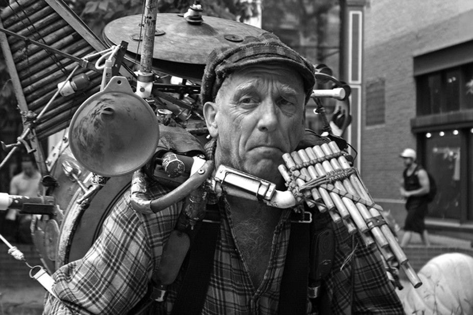 this is my photograph of a man who had a hundred instruments strapped to his back and still playe...