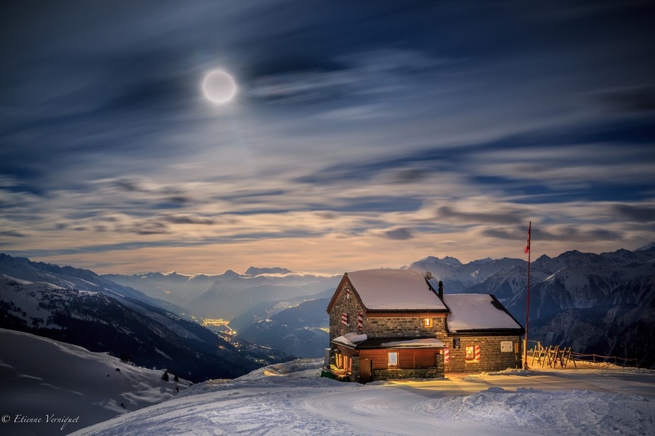 Full moon rising over the Cabane des Violettes in Switzerland (Valais). Winter scenery, long expo...