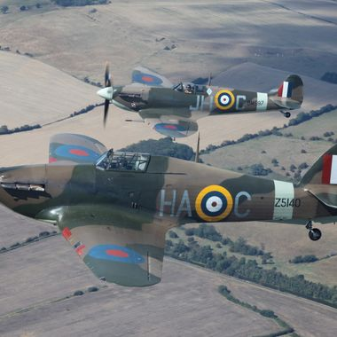Hurricane and Spitfire flying over the Kent countryside.