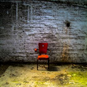 A dark empty room and lone chair.