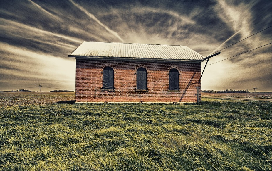 An old schoolhouse where now farming equipment is stored.
