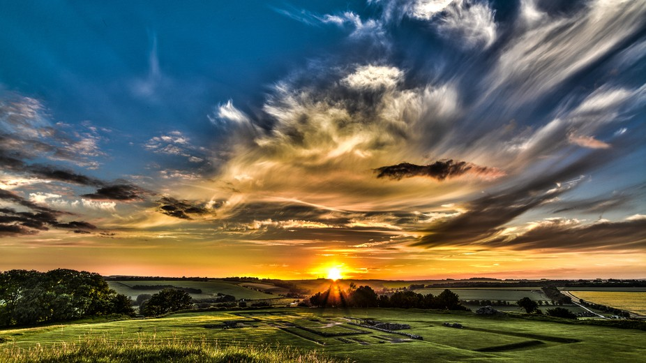 Sunset from Old Sarum hill fort in Salisbury, UK. The ancient foundations of an old cathedral are...