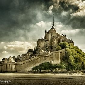 Some people walking alone around the majestuous Mont St-Michel in France