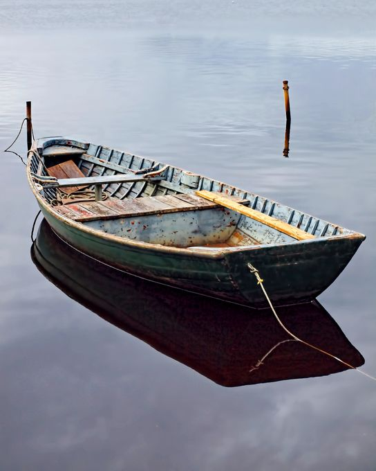 Huon Pine dinghy floating on the still waters at Mill Bay, Strahan, Tasmania