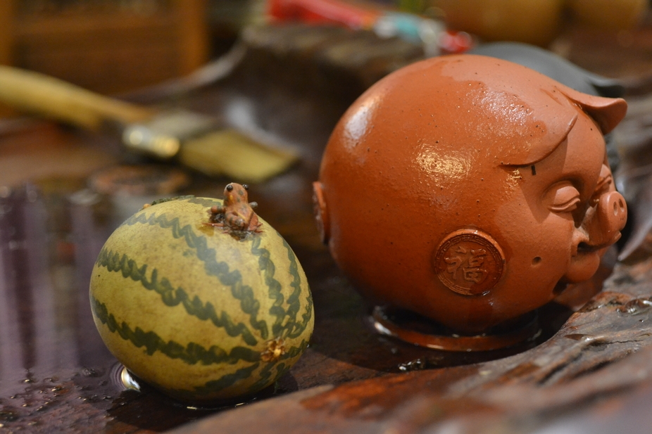 This tiny frog sits on a watermelon, next to his companion, a pig.  They are on the tea table of ...