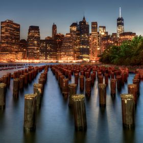 An remains of an old pier across from the NY City skyline.