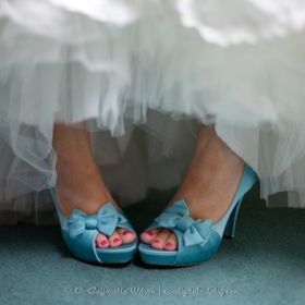 Bride's turquoise shoes turned in playfully with crinoline showing