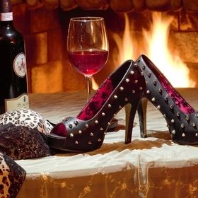 woman relaxing by the fire with a glass of wine, bra flung off, spike heels kicked off from a long hard day at work