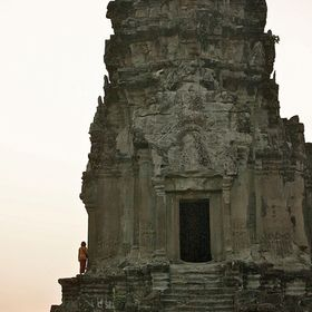 A man stands, looking so small against the ruins of Angkor Wat in Siem Reap, Cambodia.