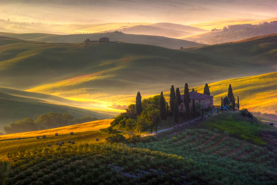 Tuscan morning, a perfect sunrise over the lonely farm house surrounded by the green and golden h...