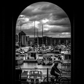 A black and white shot taken through an arch as a cyclist rides past with Swansea Marina in the background.