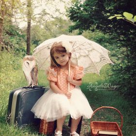 Beautiful portrait of a little girl with an umbrella and pet barn owl in the forest with a vintage look for a imagination or freedom concept.