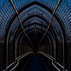 A railroad pedestrian overpass taken during the last few minutes of the Golden Hour is transformed into a dark and foreboding passageway via the ...