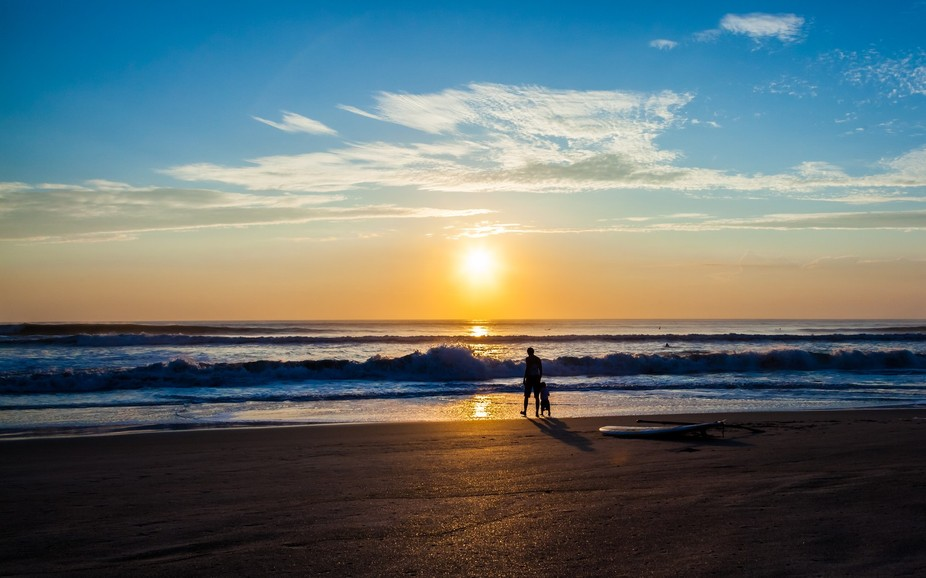 A father and his young son enjoy some quiet time as the sun rises over the ocean to begin a new day.