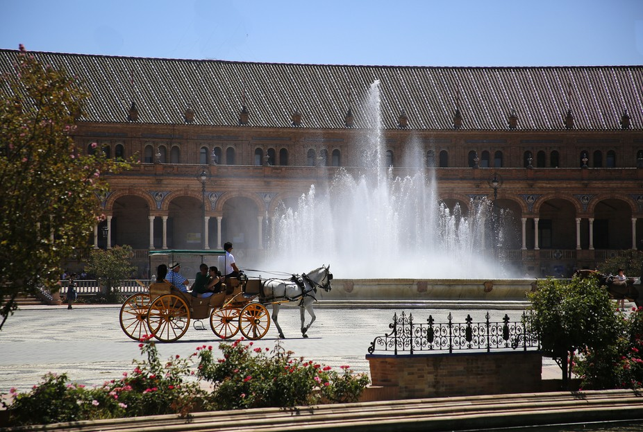 Horse Drawn Carriage passing the fountain in The Plaza Espanya, Seville