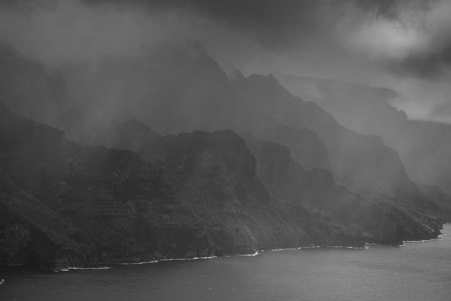 Receding tones of Napali Cliffs, softened by afternoon light and rain clouds, shot from helicopte...