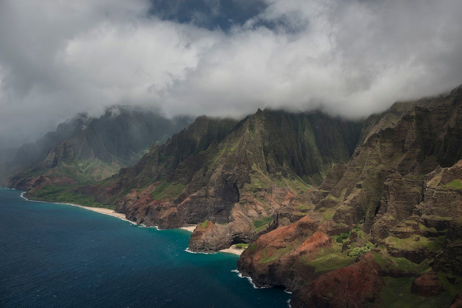 Aerial view of Napali Coast shows isolated beaches, turquoise water and shapely cliffs, topped wi...