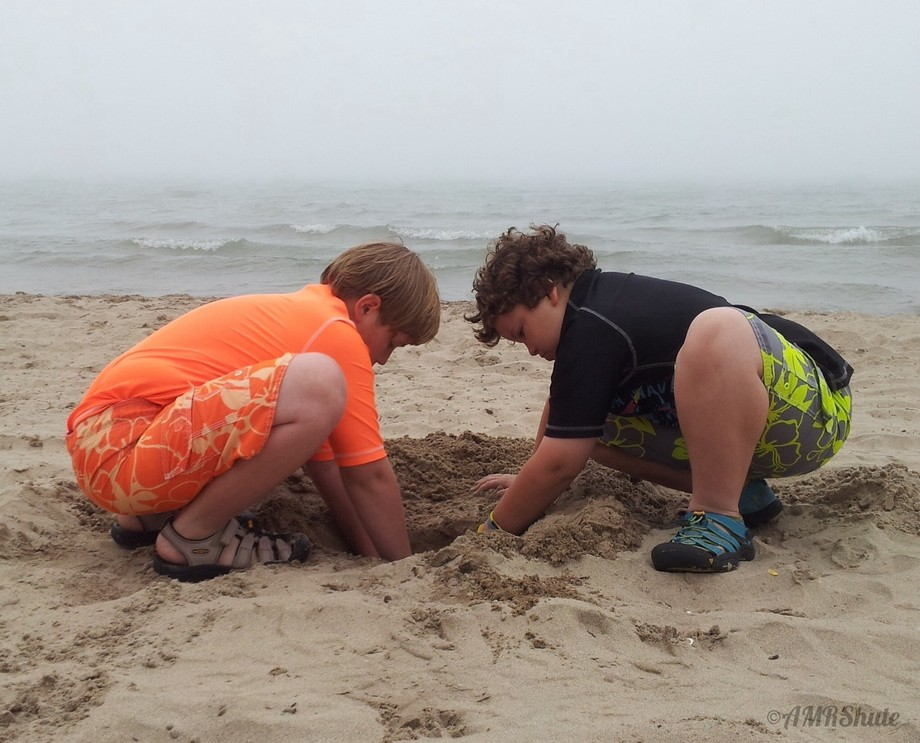 Two brothers digging in the sand on Lake Michigan on a summer day. By AMRShute