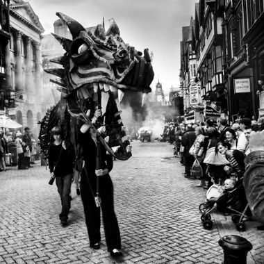 A fearsome dragon stalks the streets of Chester during a Carnival