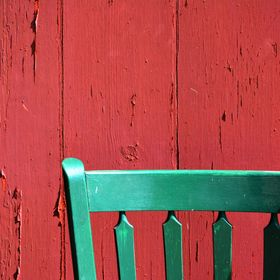 A green chair against a red wall at Hopewell Furnace in Pennsylvania