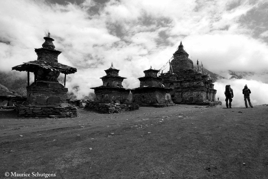 Two trekkers view the valley before lost in the clouds as timeless buddhist temples stand watch. ...