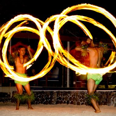 These guys were part of a show. They had a number of fire twirling acts. Flash and slow shutter gave the path of the flame and an image of the guys.