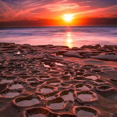 The sun sets behind an alien-looking seashore in La Jolla, California.