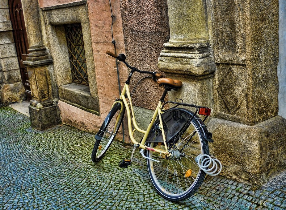 simple bicycle leaning against an old building in an elaborately tiled alley